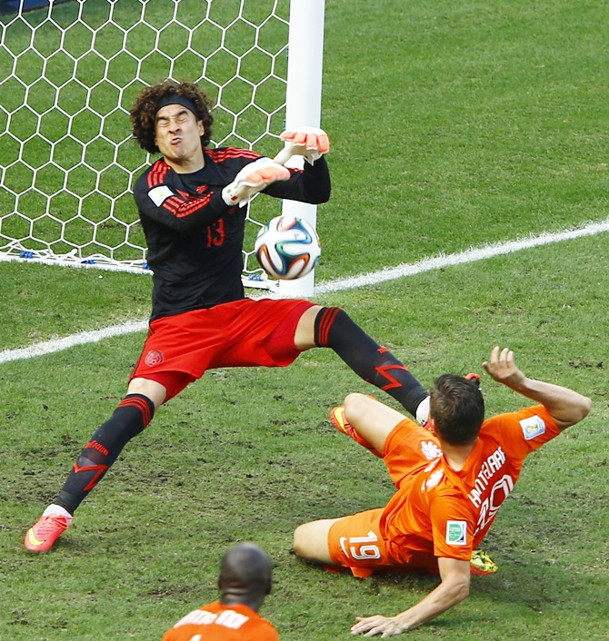 Mexico's goalkeeper Guillermo Ochoa saves a goal shot by Klaas-Jan Huntelaar of the Netherlands