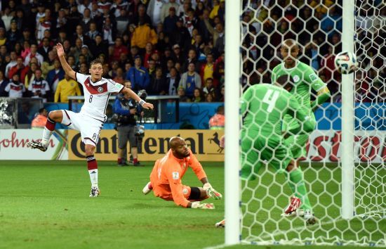 Mesut Oezil of Germany scores his team's second goal past Rais M'Bolhi of Algeria
