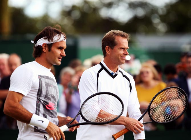 Roger Federer (left) speaks to his coach Stefan Edberg