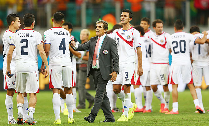 Head coach Jorge Luis Pinto of Costa Rica consoles his players after a defeat to the Netherlands in a penalty shootout in the World Cup quarter-finals on Saturday