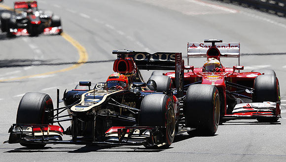 Lotus Formula One driver Kimi Raikkonen (left) steers his car ahead of Ferrari's driver Fernando Alonso