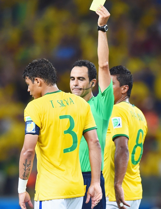 Thiago Silva of Brazil is shown a yellow card by referee Carlos Velasco Carballo   during the 2014 FIFA World Cup Brazil Quarter Final match between Brazil and Colombia at Castelao
