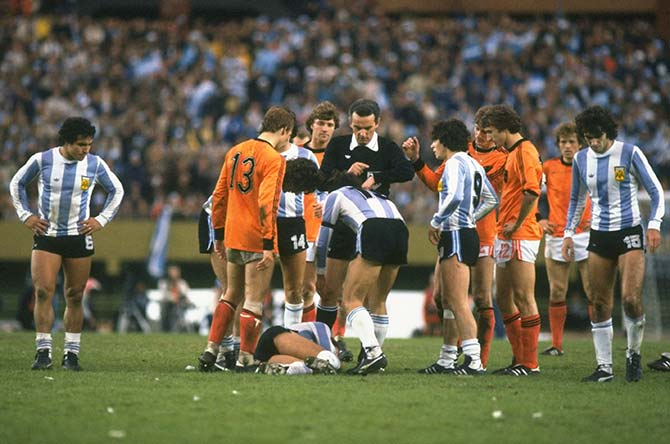 Gonella, the referee (centre) of Italy looks at his watch as an Argentinan player lies injured on the ground during the final at the Monumental Stadium in Buenos Aires
