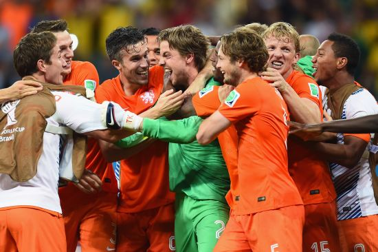 Goalkeeper Tim Krul of the Netherlands celebrates with teammates after making a save in a penalty shootout to defeat Costa Rica