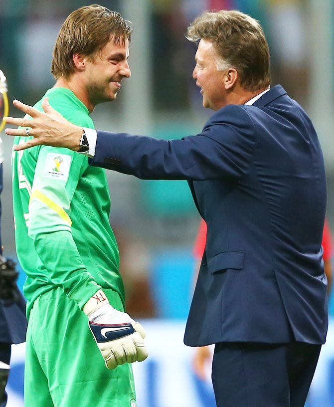 Goalkeeper Tim Krul of the Netherlands celebrates with head coach Louis van Gaal