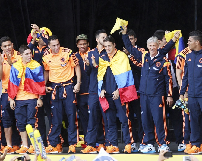Colombia's national coach Jose Pekerman (second right) and soccer team players greet fans after arriving at Bolivar park in Bogota