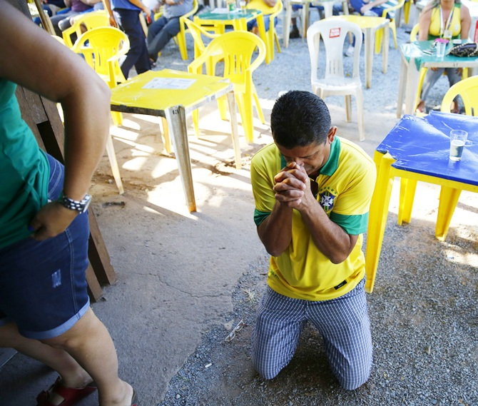 A Brazil fan prays