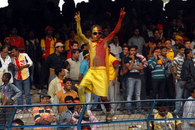 An East Bengal fan enjoys the action during a derby match