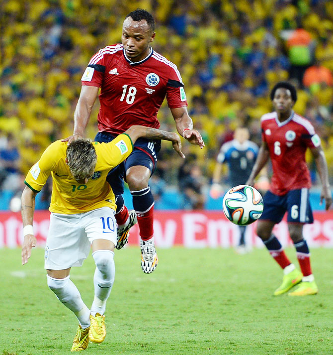 Neymar of Brazil is challenged by Juan Camilo Zuniga of Colombia during their 2014 FIFA World Cup quarter-final at Castelao in Fortaleza on July 4, 2014