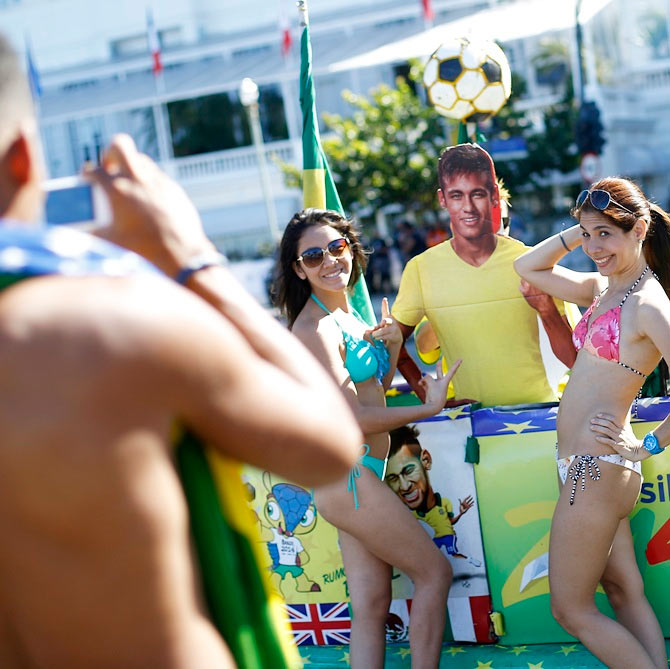 Tourists pose with a Brazilian soccer fan (C, obscured) holding an image of Neymar, inside her car which has been decorated to celebrate the 2014 World Cup, in Copacabana beach in Rio de Janeiro