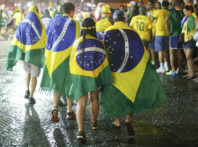 Brazil soccer fans walk in the rain after watching a broadcast of their team's loss against Germany in their 2014 World Cup semi-final match, in Rio de Janeiro on Tuesday