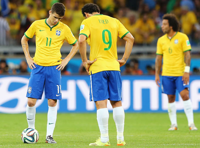 Oscar and Fred of Brazil prepare to kick off after allowing Germany to tak the lead during their semi-final against Germany at Estadio Mineirao in Belo Horizonte on Tuesday