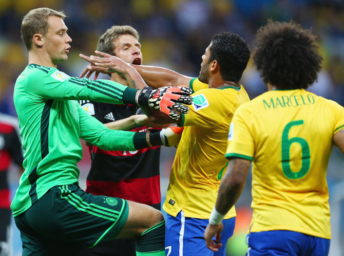 Goalkeeper Manuel Neuer of Germany separates Thomas Mueller of Germany and Hulk of Brazil after a challenge in the box during their semi-final on Tuesday