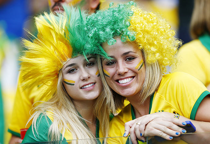 Fans of Brazil pose for pictures as they wait for the start of their 2014 World Cup semi-finals against Germany at the Mineirao stadium in Belo Horizonte on Tuesday