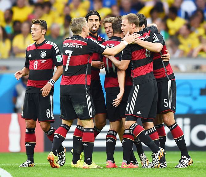 The German players celebrate with scorer Thomas Mueller after their first goal