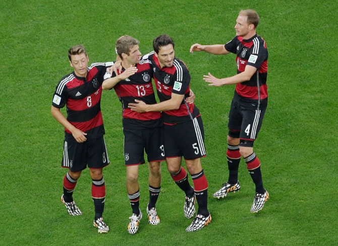 Thomas Mueller of Germany celebrates scoring his team's first goal with Mats Hummels, Mesut Oezil (left) and Benedikt Hoewedes