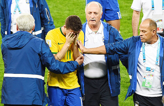 Head coach Luiz Felipe Scolari of Brazil and staff console Oscar after a 7-1 defeat to Germany on Tuesday