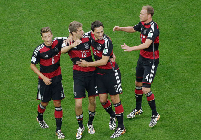 Thomas Mueller of Germany celebrates scoring his team's first goal with Mats Hummels, Mesut Oezil (left) and Benedikt Hoewedes on Tuesday