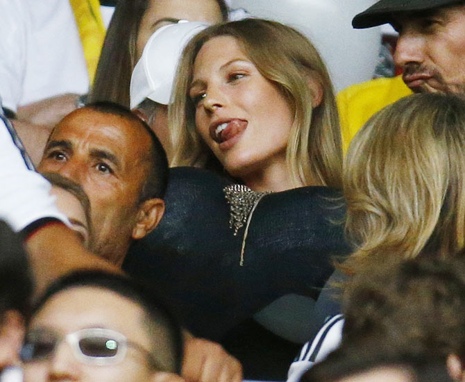 Sarah Brandner, girlfriend of Germany's Bastian Schweinsteiger, reacts after putting balloons under her shirt as she waits for the start of the 2014 World Cup semi-finals between Brazil and Germany at the Mineirao stadium in Belo Horizonte on Tuesday