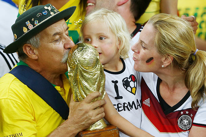 A Brazil fan and young Germany fan kiss a replica of the World Cup trophy after Germany's 7-1 win on Tuesday