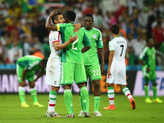 Reza Ghoochannejhad of Iran reacts with Joseph Yobo of Nigeria after their draw