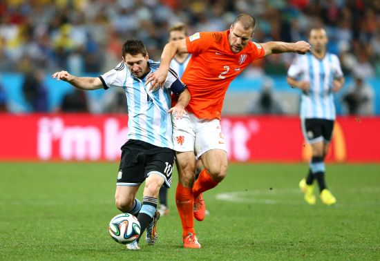 Lionel Messi of Argentina is challenged by Ron Vlaar of the Netherlands
