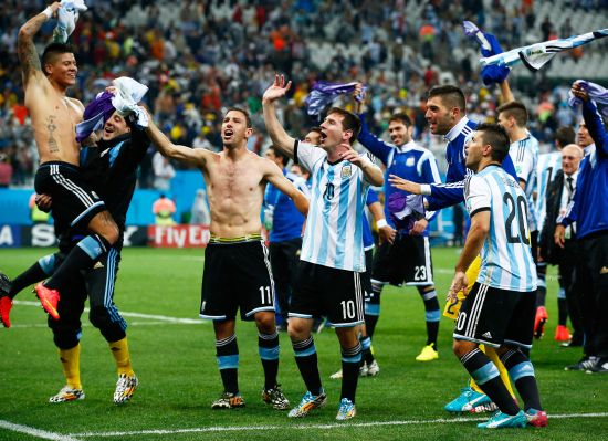 Lionel Messi of Argentina celebrates with teammates after defeating the Netherlands