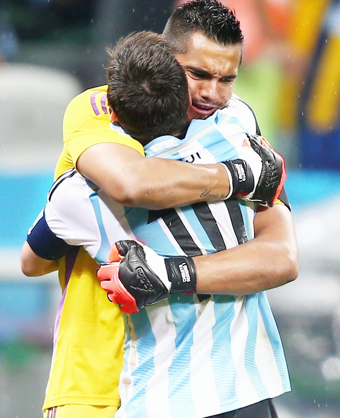 Lionel Messi and goalkeeper Sergio Romero of Argentina react after Messi's made penalty kick in a shootout