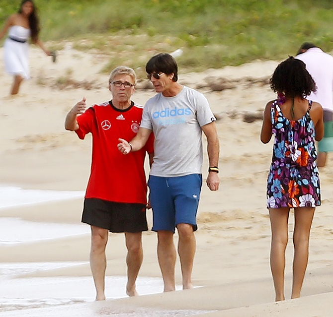 Germany's coach Joachim Loew listens to head match analyst Urs Siegenthaler, left, as they walk on the beach in front of their base camp Campo Bahia, in the village of Santo Andre north of Porto Seguro