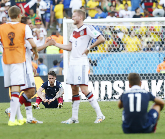 France's Mathieu Debuchy (bottom left) and his teammate Antoine Griezmann, right,   react as Germany's Andre Schuerrle, centre, celebrates with his teammates