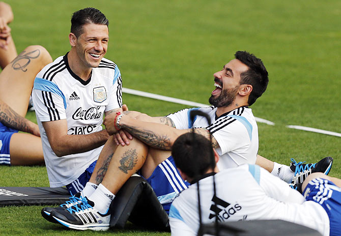 Argentina's players Martin Demichelis (left) and Ezequiel Lavezzi share a joke with Lionel Messi (right, bottom) during a training session in Vespasiano on Thursday