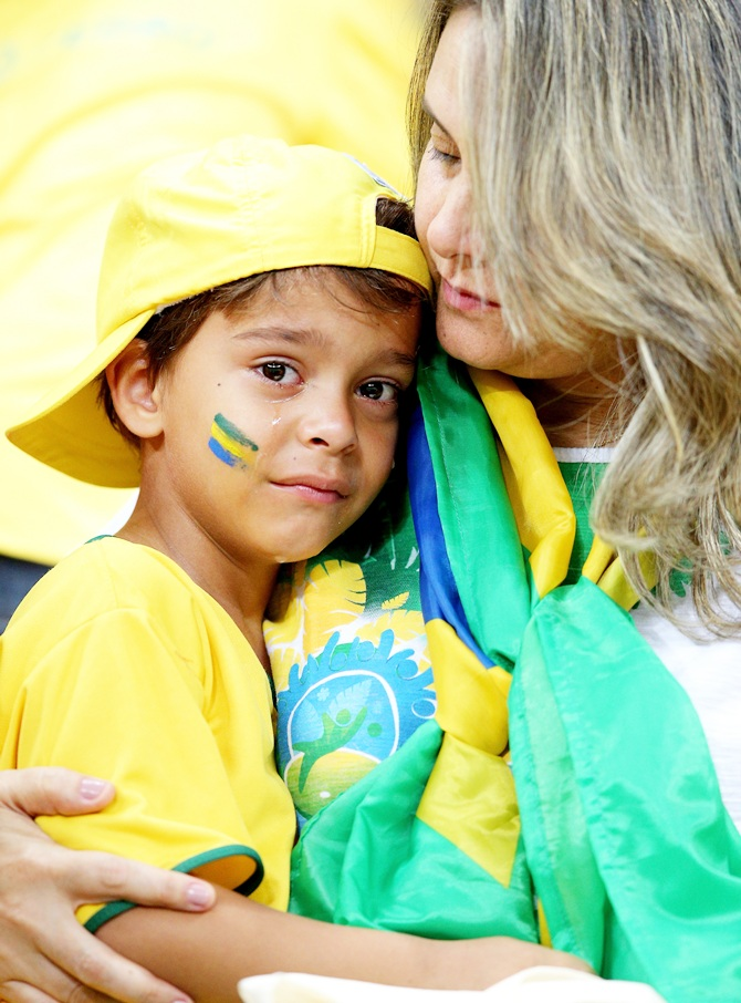 A young Brazil fan is consoled after being defeated by the Netherlands