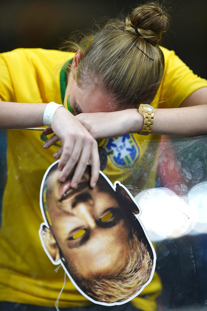 A dejected Brazil fan holding a Neymar mask reacts
