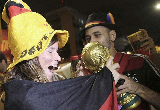 Germany soccer fans celebrate with a replica of the World Cup trophy in front of Maracana stadium at the end of the World Cup final on Sunday