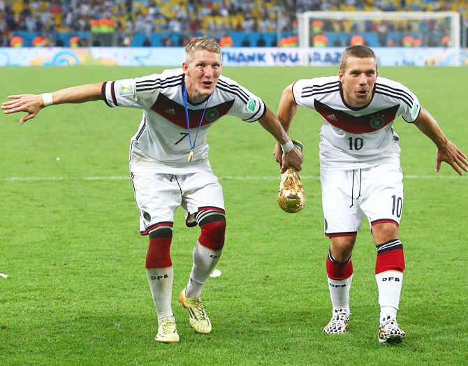 Bastian Schweinsteiger and Lukas Podolski of Germany celebrate with the World Cup trophy after defeating Argentina 1-0 in extra time