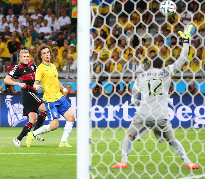 Andre Schuerrle of Germany scores his team's seventh goal past Julio Cesar of Brazil
