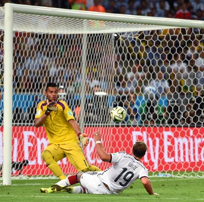 Mario Goetze of Germany slips the ball past Argentina goalkeeper Sergio Romero in the World Cup final on Sunday.