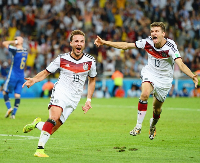Mario Goetze of Germany, left, celebrates scoring his team's goal with Thomas Mueller