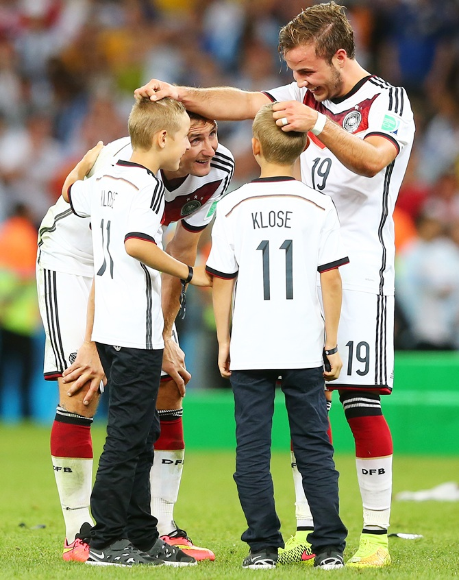 Mario Goetze, Miroslav Klose of Germany and sons celebrate after defeating Argentina 1-0 in extra time
