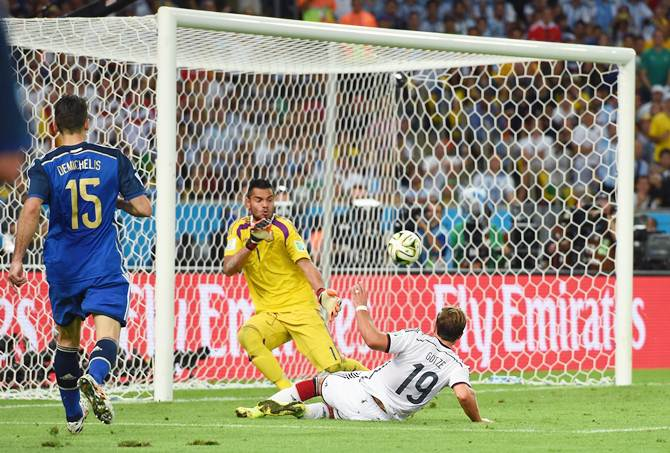 Mario Goetze of Germany slips the ball past Argentina goalkeeper Sergio Romero in the World Cup final