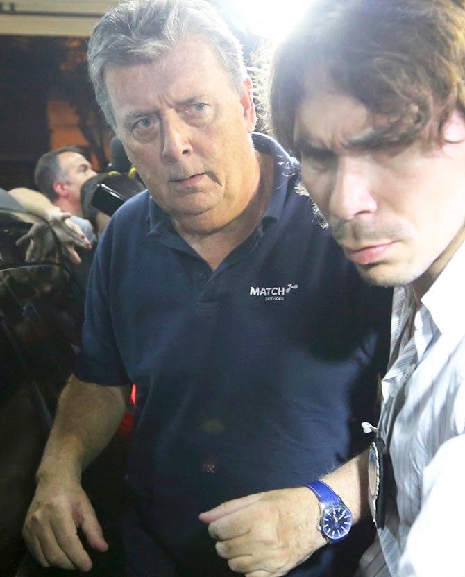 Ray Whelan, left, of Switzerland-based Match Services, arrives at a police station after being arrested in Rio de Janeiro