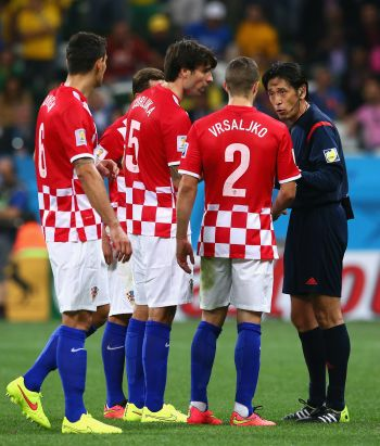 Referee Yuichi Nishimura speaks to Dejan Lovren, Vedran Corluka and Sime Vrsaljko of Croatia after awarding a penalty kick