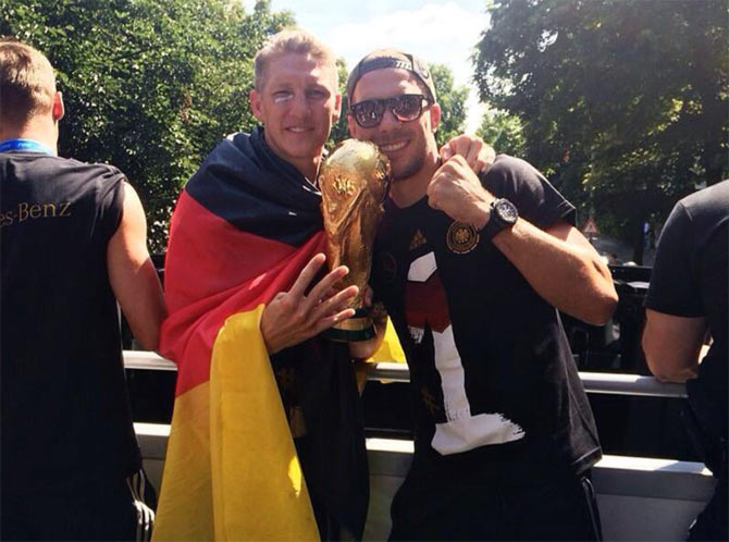 Lukas Podolski and Bastian Schweinsteiger celebrate with the World Cup atop the bus on Tuesday