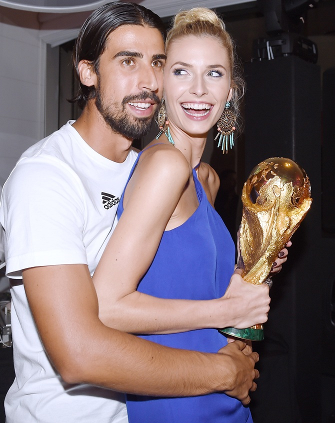 Sami Khedira of Germany and girlfriend Lena Gercke pose with the World Cup trophy as   he celebrates with teammates at a party, after winning the 2014 FIFA World Cup