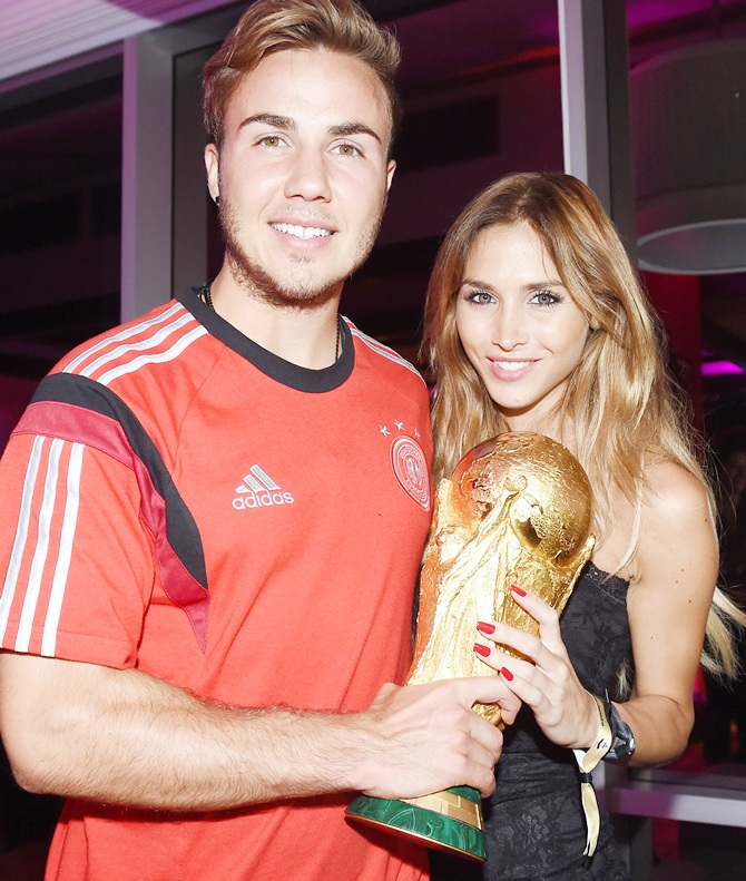 Goalscorer Mario Gotze of Germany and girlfriend Ann-Kathrin Brommel pose with the World Cup tro