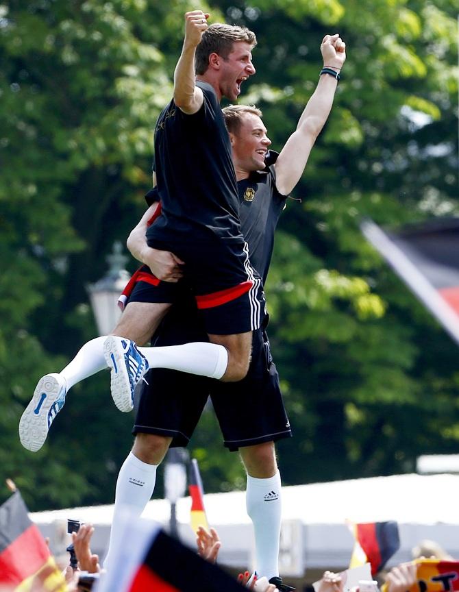 Germany's goalkeeper Manuel Neuer carries Thomas Mueller