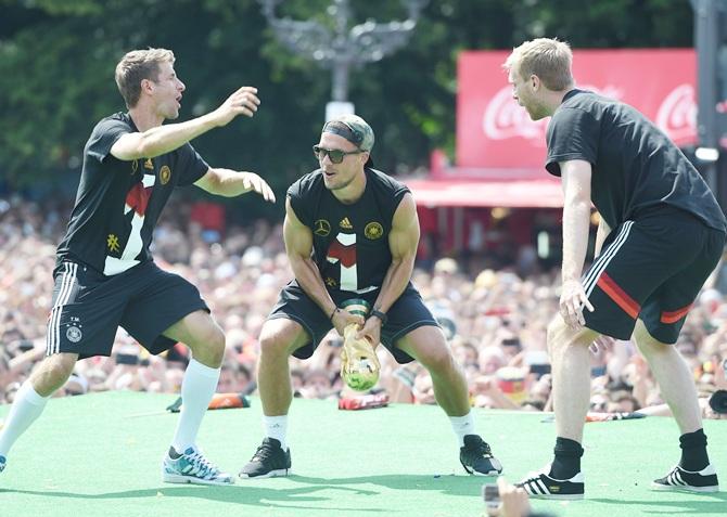 Per Mertesacker, right, Lukas Podolski, centre, and Thomas Meuller, left, celebrate on stage