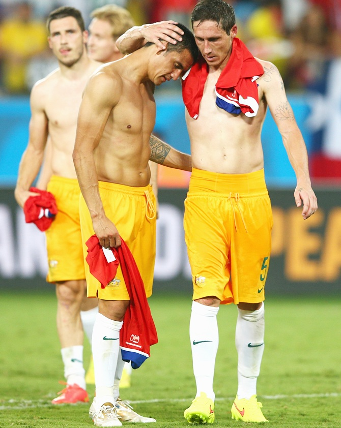 Tim Cahill, left, and Mark Milligan of Australia embrace after being defeated by Chile