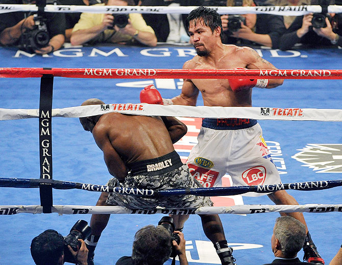 Manny Pacquiao (right) pushes Timothy Bradley on the ropes