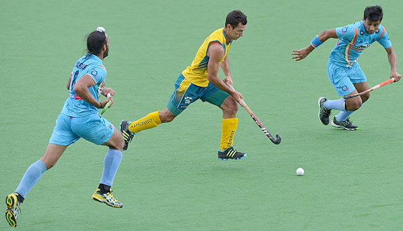Jamie Dwyer of Australia (centre) runs between India's Manpreet Singh (left) and Sadar Singh (right)